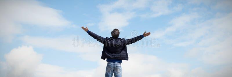 Zusammengesetztes Bild der hinteren Ansicht eines Mannes, der oben seine Arme anhebt lizenzfreie stockbilder