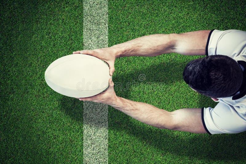 Zusammengesetztes Bild der hohen Winkelsicht des Mannes Rugbyball mit beiden Händen halten lizenzfreie stockfotografie