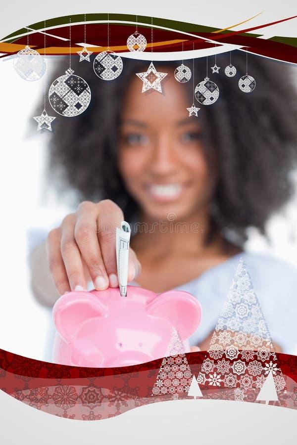 Zusammengesetztes Bild der jungen Frau Anmerkungen in ein Sparschwein einfügend lizenzfreies stockfoto