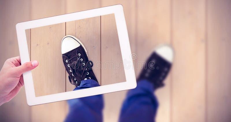 Zusammengesetztes Bild der männlichen Hand Tablette halten stockbilder