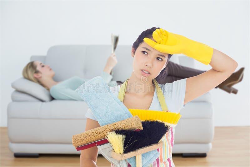 Zusammengesetztes Bild der müden Frau Reinigungswerkzeuge halten lizenzfreie stockbilder