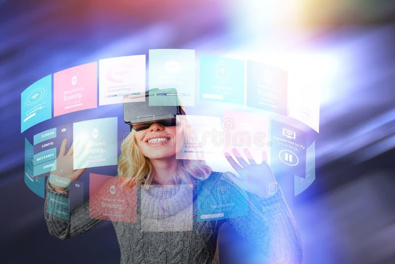 Zusammengesetztes Bild der netten jungen Frau, die virtuellen Kopfhörer der Wirklichkeit verwendet lizenzfreies stockfoto