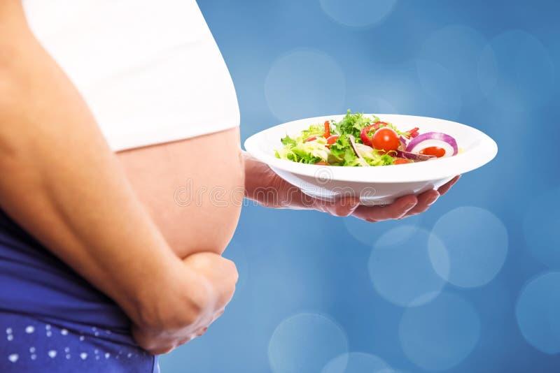 Zusammengesetztes Bild der schwangeren Frau einen Salat essend stockfoto