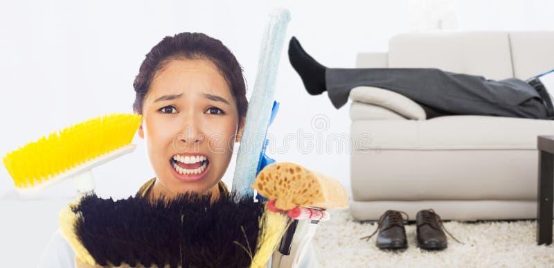 Zusammengesetztes Bild der sehr betonten Frau mit Reinigungswerkzeugen lizenzfreies stockfoto