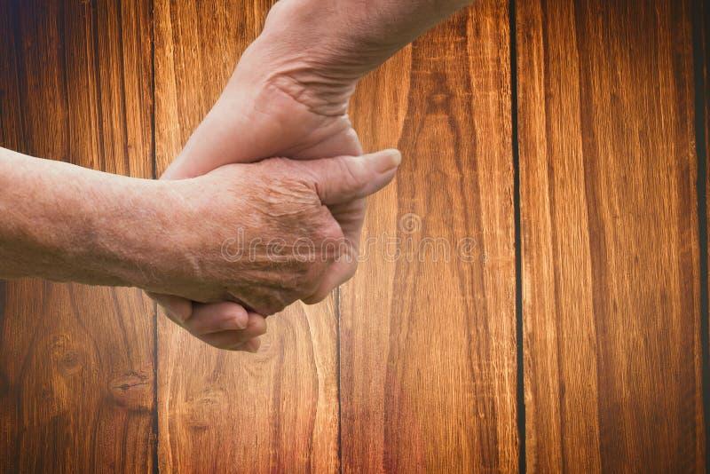Zusammengesetztes Bild des älteren Paarhändchenhaltens lizenzfreie stockfotografie