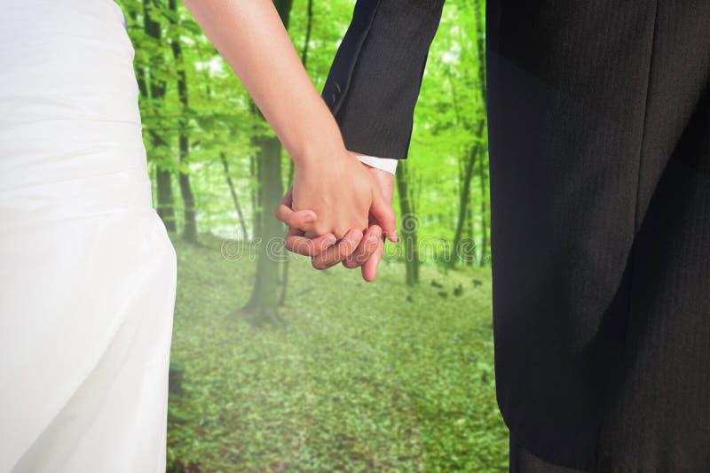 Zusammengesetztes Bild des Abschlusses oben der netten jungen Jungvermählten, die ihre Hände halten stockbilder