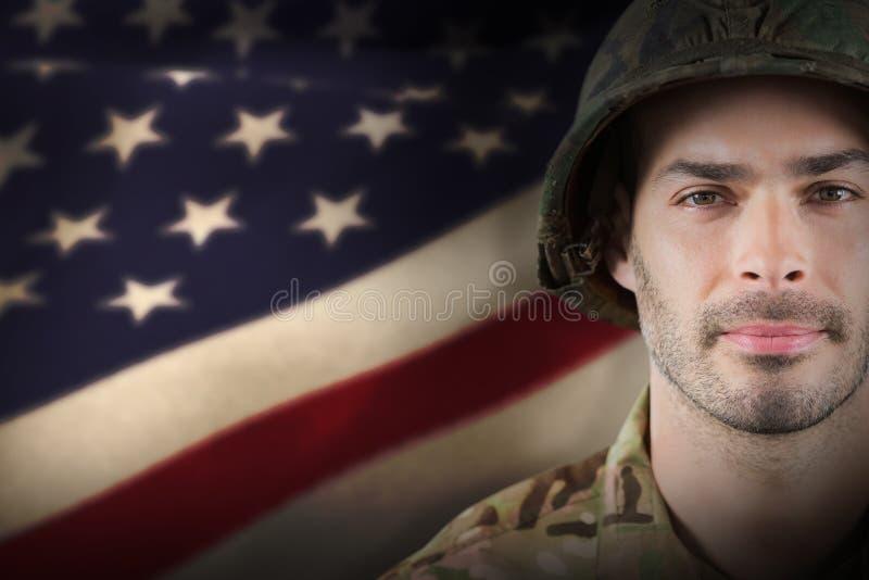 Zusammengesetztes Bild des Abschlusses oben des tragenden Schutzhelms des überzeugten Soldaten lizenzfreies stockbild
