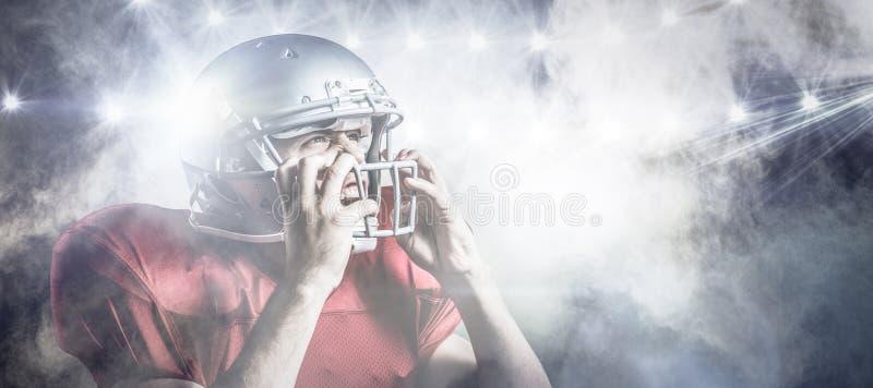 Zusammengesetztes Bild des aggressiven Spielers des amerikanischen Fußballs, der Sturzhelm hält lizenzfreie stockfotografie