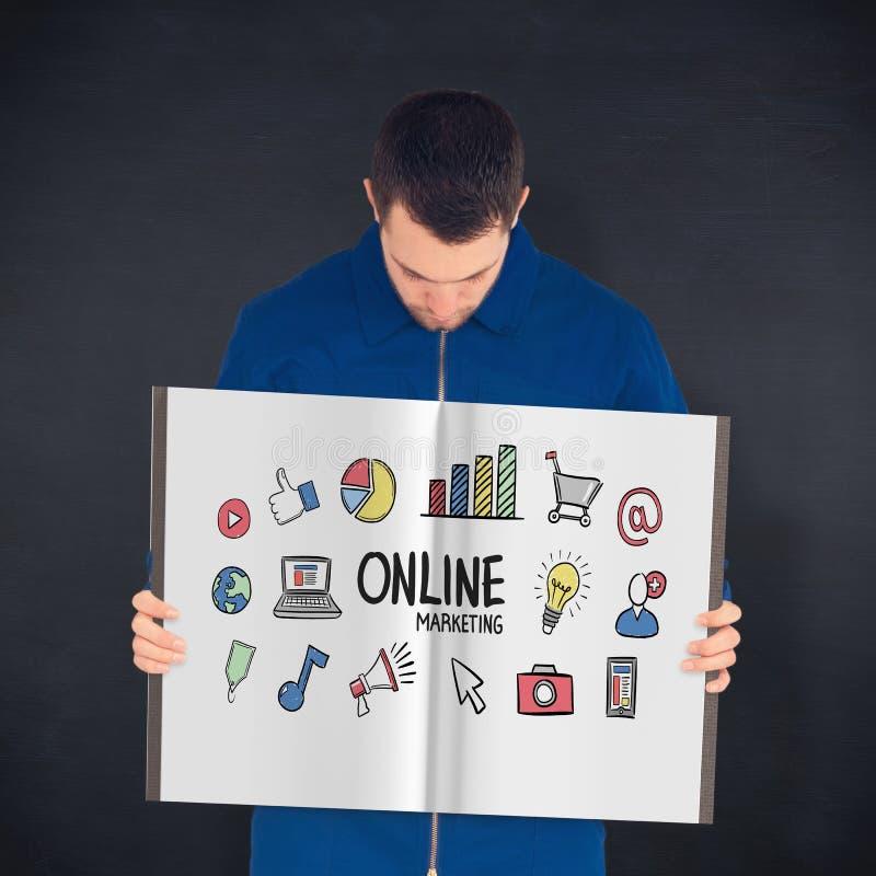 Zusammengesetztes Bild des Arbeiters ein Buch zeigend lizenzfreies stockfoto