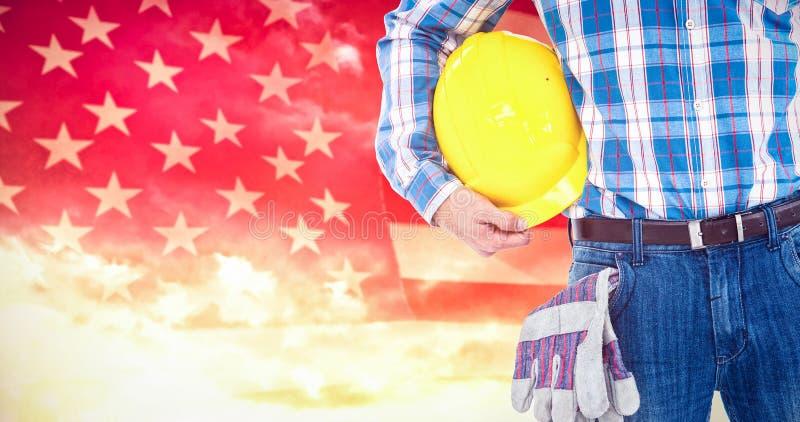 Zusammengesetztes Bild des Arbeiters mit Schutzhelm und Handschuhen lizenzfreies stockfoto