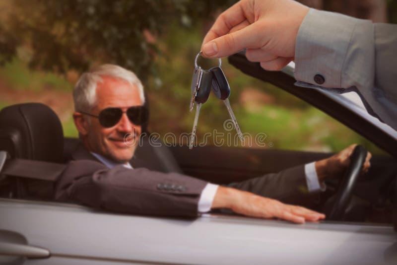Zusammengesetztes Bild des Autohändlers Schlüssel gebend einem Kunden stockfotografie