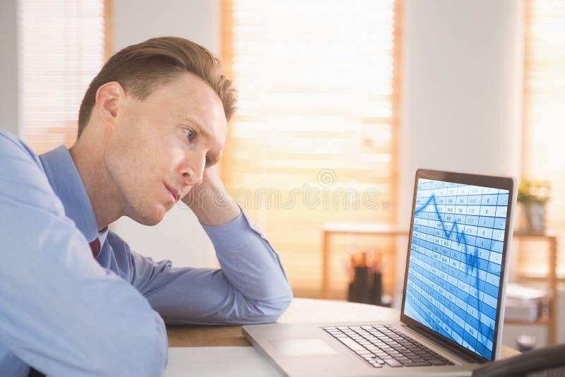 Zusammengesetztes Bild des fokussierten Geschäftsmannes, der Laptop betrachtet lizenzfreie stockfotografie