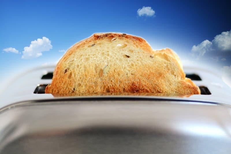 Zusammengesetztes Bild des gebratenen Brotes im silbernen Toaster gegen blauen Himmel stockfotografie