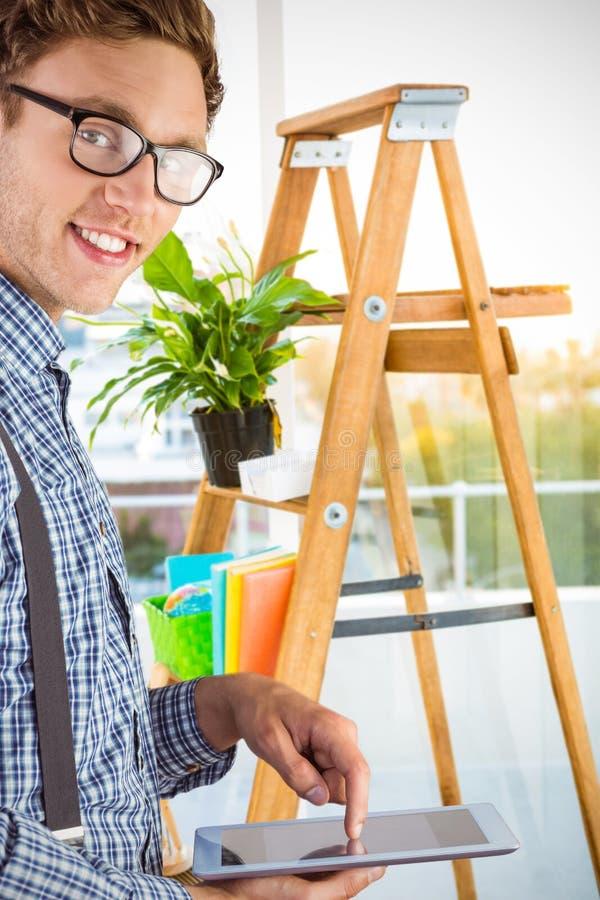 Zusammengesetztes Bild des geeky Geschäftsmannes unter Verwendung seines Tabletten-PC stockfotos
