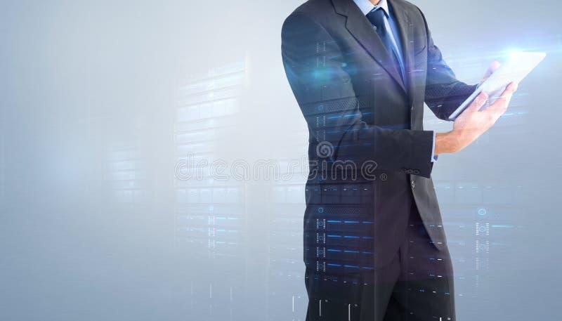 Zusammengesetztes Bild des Geschäftsmannes die Kamera bei der Anwendung seiner Tablette betrachtend lizenzfreie stockfotografie
