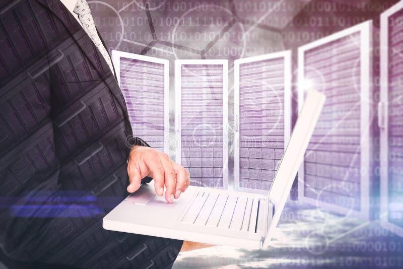 Zusammengesetztes Bild des Geschäftsmannes Laptop halten lizenzfreies stockfoto