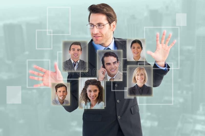 Zusammengesetztes Bild des Geschäftsmannes stehend mit den Fingern heraus verbreitet stockfotos