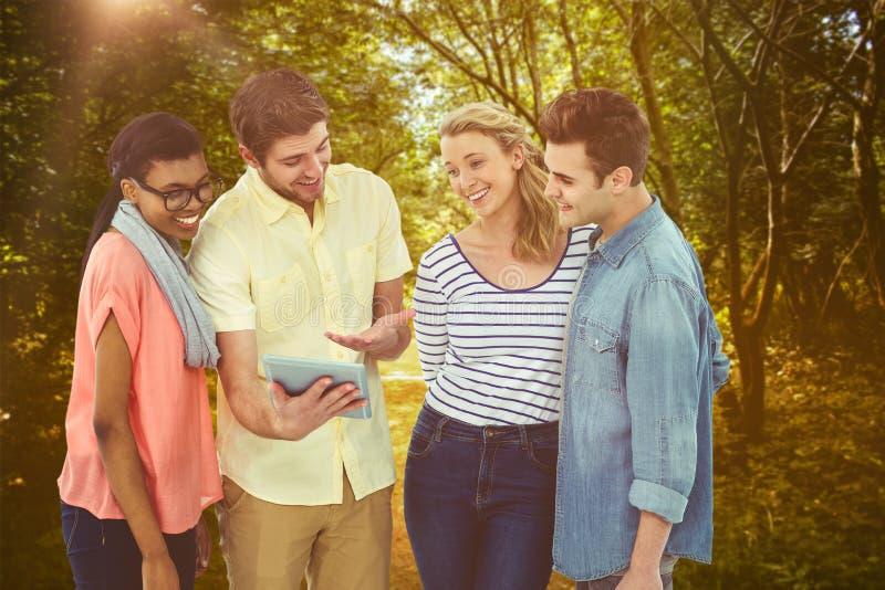 Zusammengesetztes Bild des glücklichen kreativen Teams unter Verwendung eines Tabletten-PC lizenzfreies stockfoto