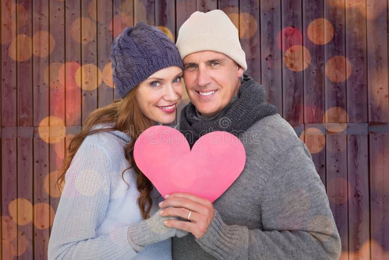 Zusammengesetztes Bild des glücklichen Paars in der warmen Kleidung, die Herz hält lizenzfreies stockbild