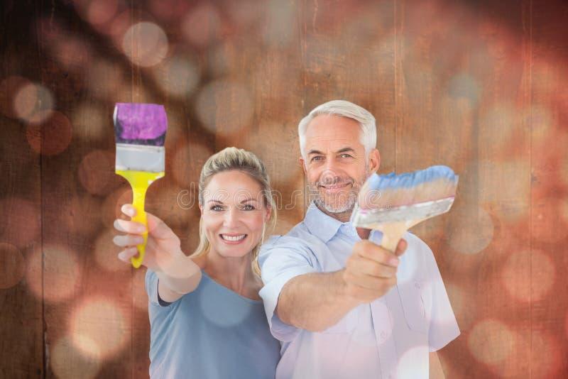 Zusammengesetztes Bild des glücklichen Paars die Malerpinsel halten, die an der Kamera lächeln lizenzfreie stockbilder