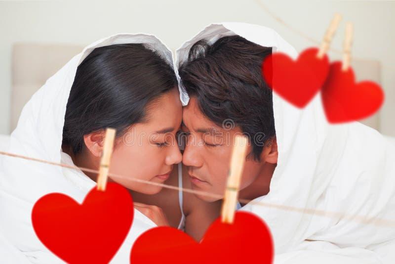 Zusammengesetztes Bild des glücklichen Paars zusammen liegend auf Bett unter der Daunendecke vektor abbildung