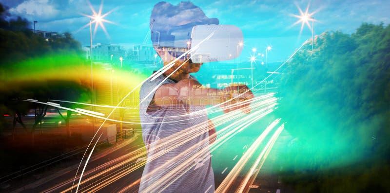 Zusammengesetztes Bild des Jungen, der Kopfhörer der virtuellen Realität beim Gestikulieren verwendet stockbilder