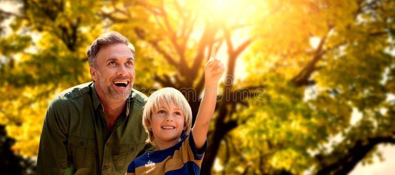 Zusammengesetztes Bild des Jungen zeigend in die Luft mit seinem Vater stockbild