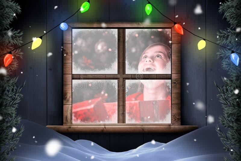 Zusammengesetztes Bild des kleinen Mädchens ein magisches Weihnachtsgeschenk öffnend stockfoto