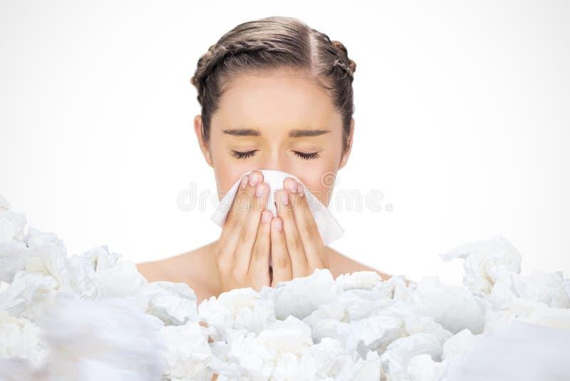 Zusammengesetztes Bild des kranken jungen Modells, das ihre Nase durchbrennt lizenzfreie stockbilder