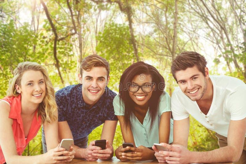 Zusammengesetztes Bild des kreativen Teams alles unter Verwendung der Smartphones stockfotografie