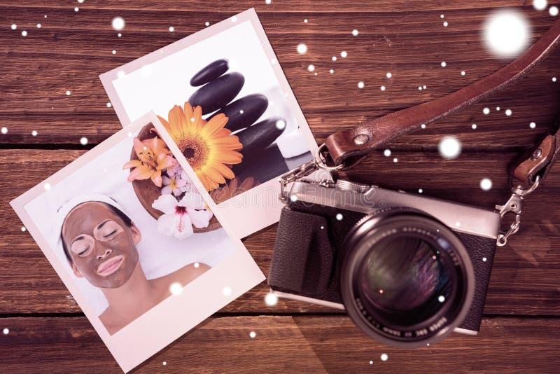 Zusammengesetztes Bild des lächelnden Brunette eine Schlammbehandlungsgesichtsbehandlung neben Schüssel Blumen erhalten lizenzfreies stockbild