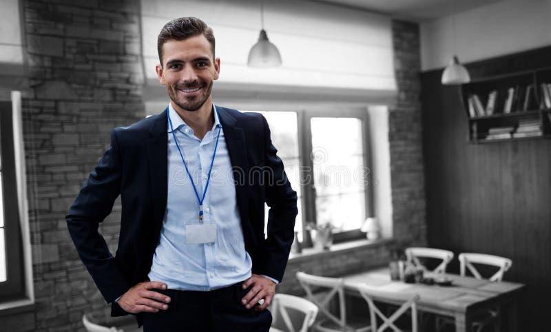 Zusammengesetztes Bild des lächelnden Geschäftsmannes mit der Hand auf der Hüfte, die Identifikation trägt lizenzfreies stockbild