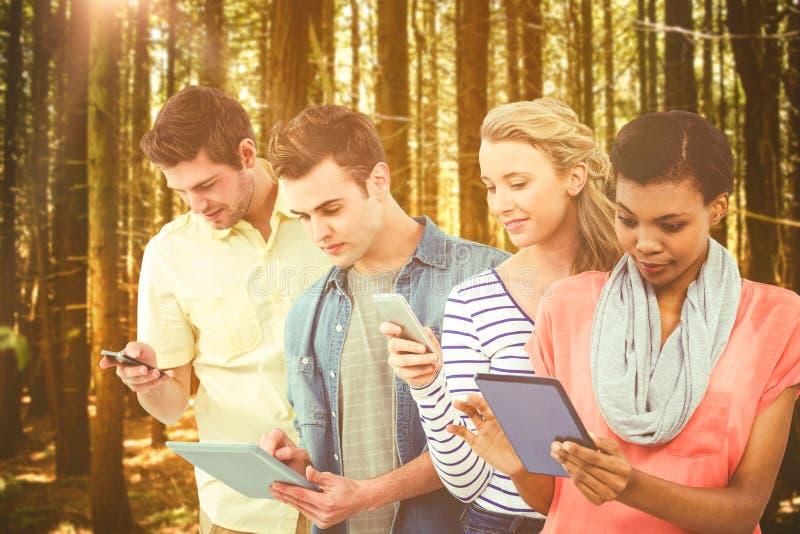 Zusammengesetztes Bild des lächelnden kreativen Teams, das in einer Linie unter Verwendung der Technologie steht lizenzfreie stockfotografie