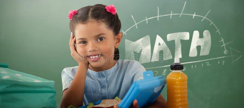 Zusammengesetztes Bild des lächelnden Mädchens mit Brotdose bei Tisch lizenzfreies stockfoto