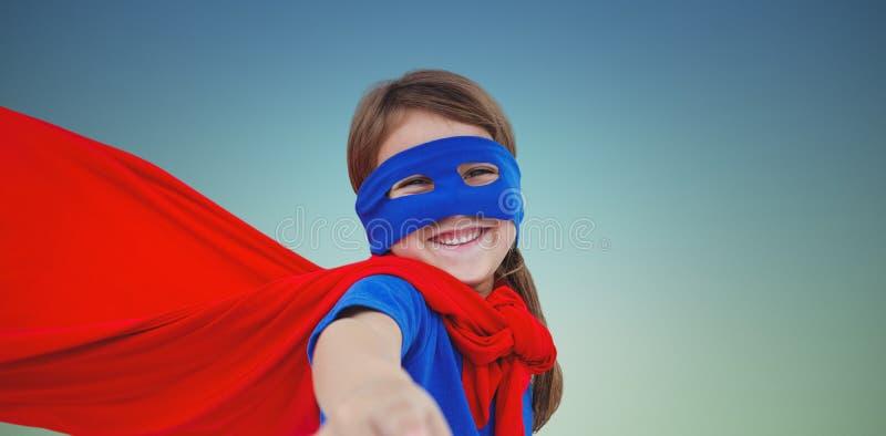 Zusammengesetztes Bild des lächelnden verdeckten Mädchens, das vortäuscht, Superheld zu sein lizenzfreie stockfotos