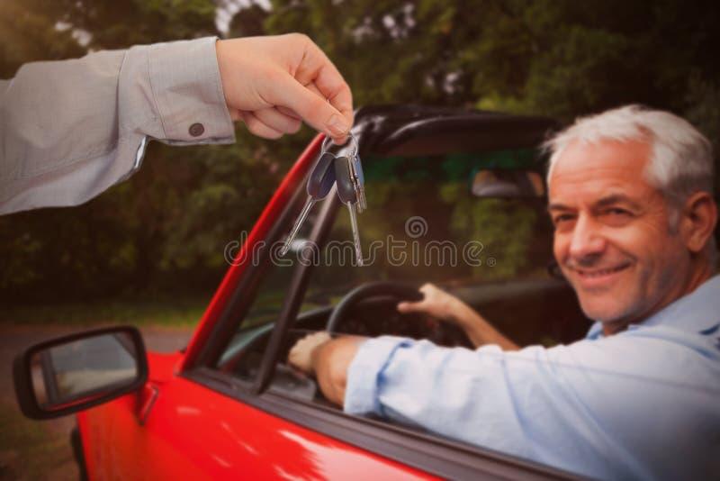 Zusammengesetztes Bild des Mannes Schlüssel gebend jemand stockfotografie