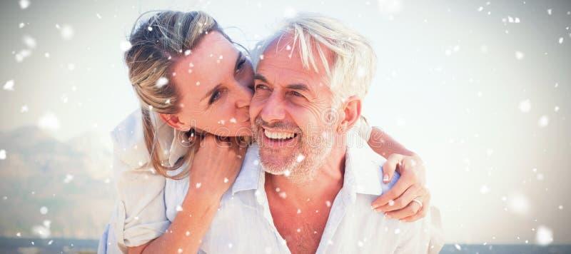 Zusammengesetztes Bild des Mannes seiner lächelnden Frau ein Doppelpol am Strand gebend lizenzfreies stockfoto