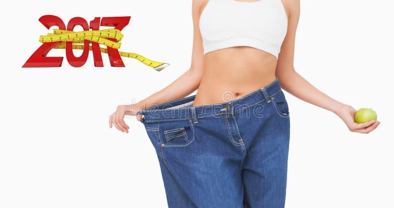 Zusammengesetztes Bild des mittleren Abschnitts der dünnen Frau die zu großen Jeans tragend, die einen Apfel halten lizenzfreies stockfoto