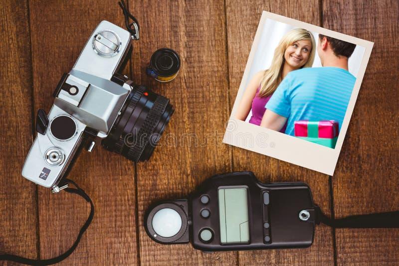 Zusammengesetztes Bild des netten Freundes ein Geschenk gebend stockbilder