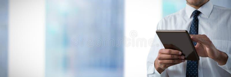 Zusammengesetztes Bild des oberen Mittelteils des Mannes, der eine Tablette verwendet stockbild