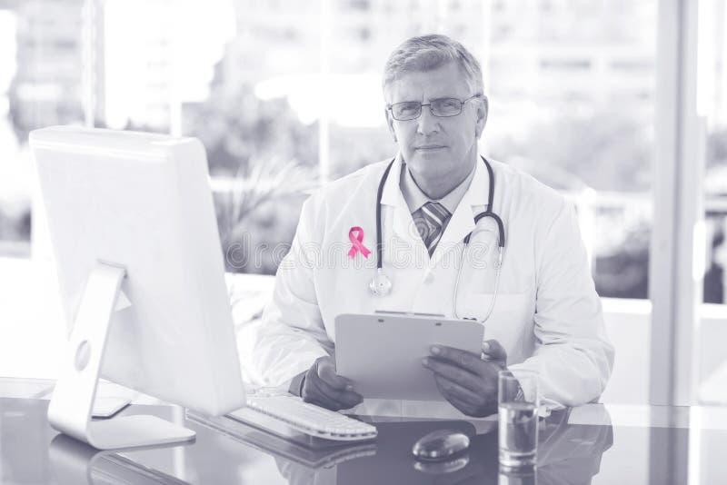 Zusammengesetztes Bild des Porträts überzeugten männlichen Doktors, der am Computertisch sitzt stockbild