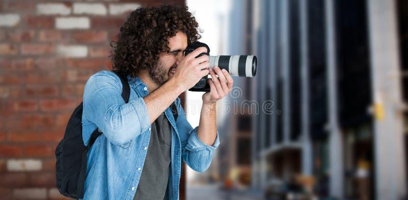 Zusammengesetztes Bild des professionellen männlichen Fotografen, der Foto macht stockfotos