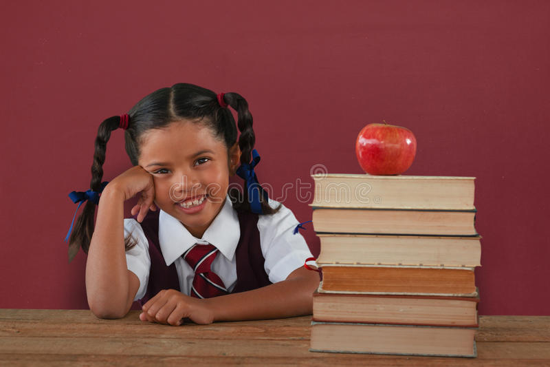 Zusammengesetztes Bild des Schulmädchens lehnend durch Bücher und Apfel auf Schreibtisch stockbild