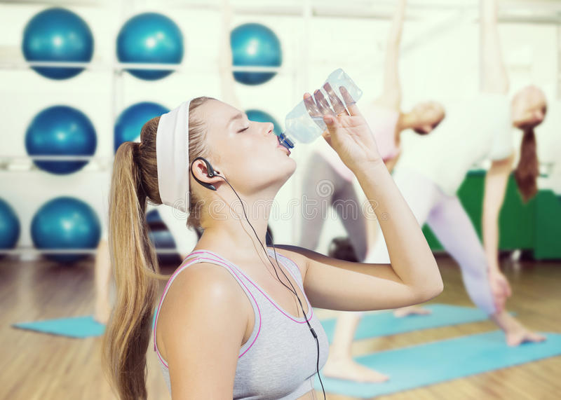 Zusammengesetztes Bild des sportlichen blonden Trinkwassers lizenzfreie stockbilder