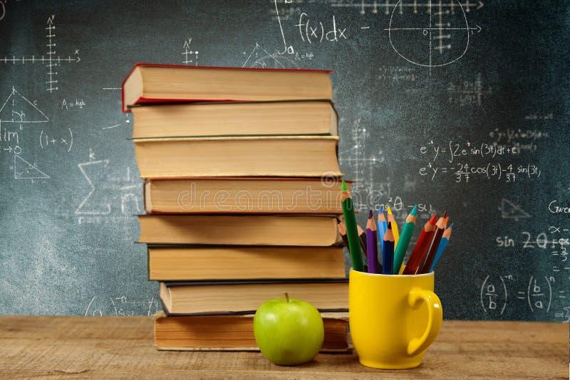 Zusammengesetztes Bild des Stapels Bücher durch farbige Bleistifte im Becher und im Apfel auf Tabelle stockfoto