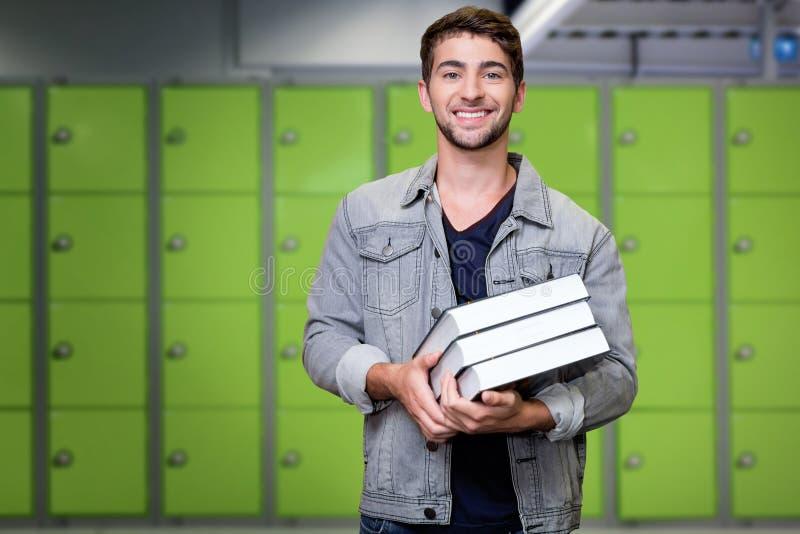 Zusammengesetztes Bild des Studenten lächelnd an der Kamera in der Bibliothek stockfotos