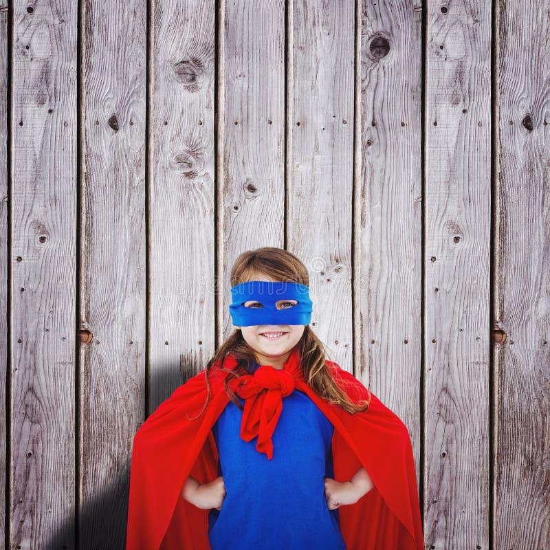 Zusammengesetztes Bild des verdeckten Mädchens, das vortäuscht, Superheld zu sein stockfotografie