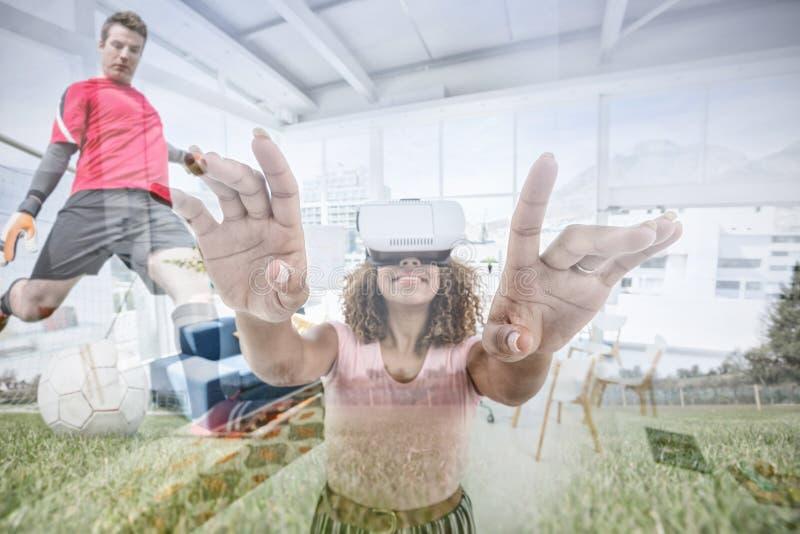 Zusammengesetztes Bild des weiblichen Exekutivgestikulierens bei der Anwendung des Kopfhörers der virtuellen Realität stockfoto