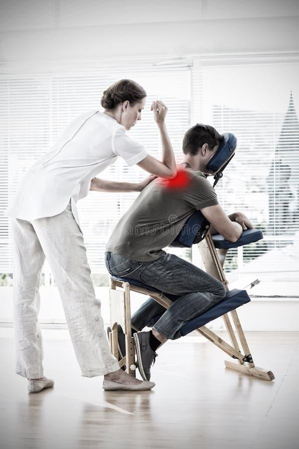 Zusammengesetztes Bild des weiblichen Therapeuten Rückenmassage gebend dem Mann stockbilder