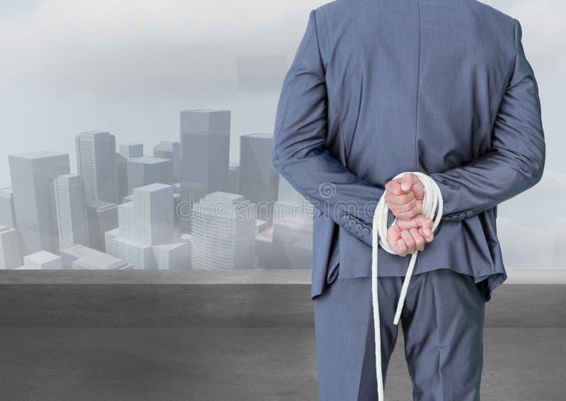 Zusammengesetztes Bild Digital eines Geschäftsmannes mit seinen Händen gebunden hinter der Rückseite lizenzfreie stockbilder